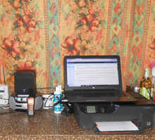 Photo of laptop and a small speaker on a kitchen countertop